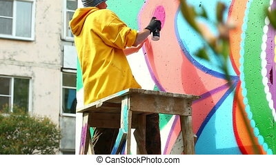 Guy drawing with paint from spray on wall - Guy drawing with...