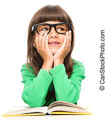 Young girl is daydreaming while reading book and wearing...