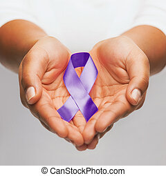 hands holding purple awareness ribbon - healthcare and...