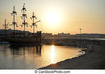 Old Pirate Ship at sea on sunrise
