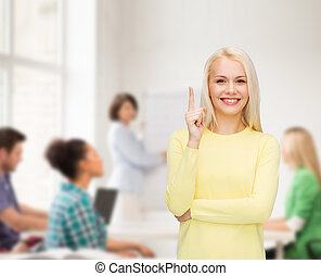 smiling woman pointing her finger up - advertisement concept...