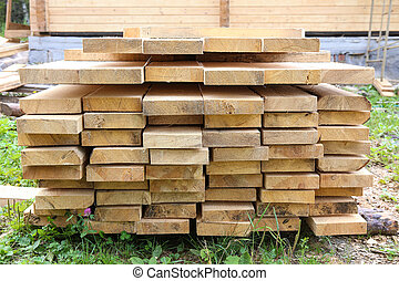 boards in stack against house - boards in stack against...
