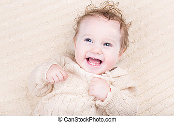 Funny laughing baby in a knitted dress