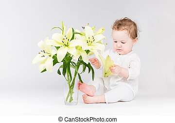 Funny little baby playing with lily flowers
