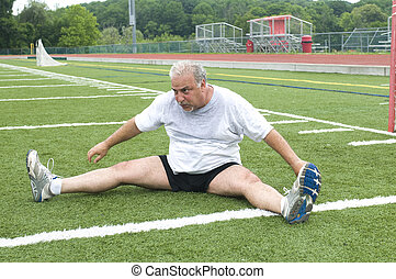 middle age man stretching and exercising on sports field -...