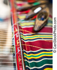 Weaving shuttles and textured textile with pattern. Artistic...