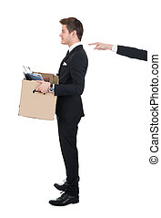 Businessman Carrying Cardboard Box With Hand Pointing At Him...