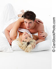 Couple lying on bed smiling at the camera
