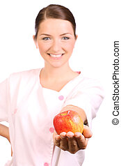 Nurse offering an apple - A beautiful young nurse offering...
