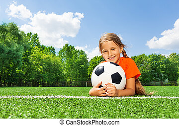 Happy girl holding football with both arms and laying on...