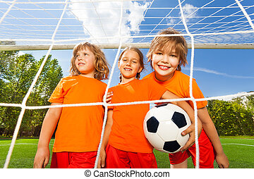 Smiling girls with football stand behind net - Three smiling...