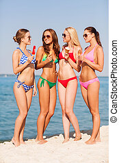 group of smiling women eating ice cream on beach - summer...