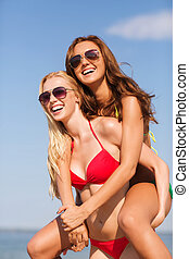 two smiling young women on beach - summer vacation,...