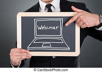 Businessman Pointing Webinar Sign Drawn On Slate -...