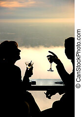 Couple having a drink in the sky - Silhouette of a young...