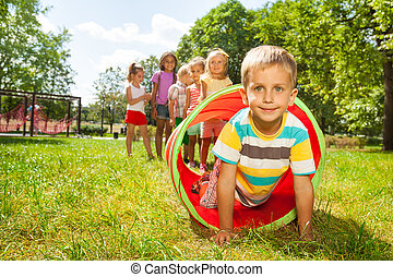 Playing crawling though tube on the lawn - Group of...
