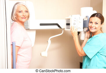 Young female doctor smiling during female patient medical...