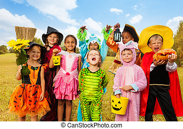 Happy excited kids in Halloween costumes stand close on...