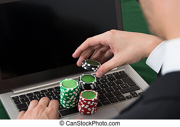 Businessman Using Laptop With Stacked Poker Chips - Cropped...
