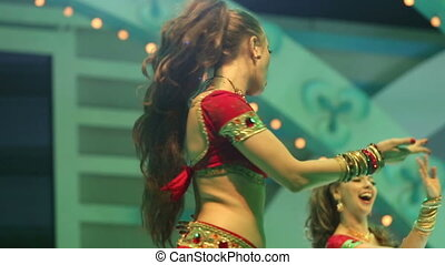 girl dancing on stage in a red national Indian suit - Artist...