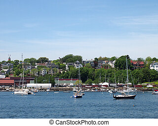 Portland Maine Coastline with boats in the water, homes on...