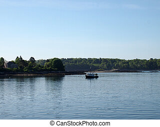 Fishing boat rests in water of Casco Bay off shore of island...