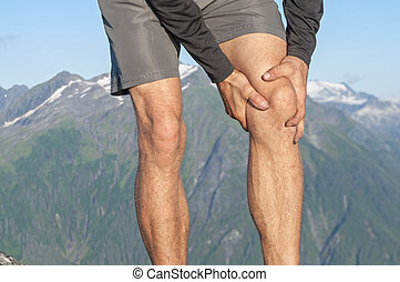 Runner with knee pain - Closeup of male runner holding...