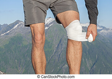 Caring for knee injury - Male runner wearing shorts on top...