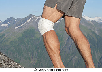 Knee sport support - Closeup of legs of male runner with...