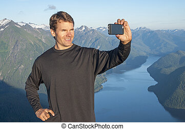 Selfie of scenic mountain view - Handsome Caucasian man...