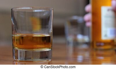 Pouring scotch whiskey in glass