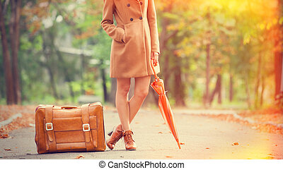 Gril in coat with umbrella and suitcase in the park.