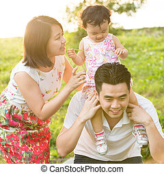 Asian family playing at outdoor park during sunset