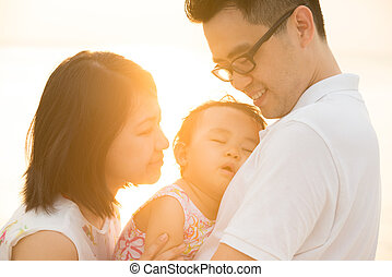 Asian family at outdoor sunset beach