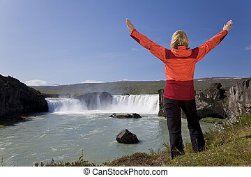 Woman Celebrating At Godafoss Waterfall, Iceland - A young...