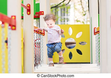 Cute baby girl walking on a playground