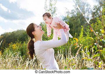 Young mother playing with her baby daughter in a beautiful sunny