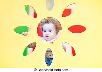 Funny baby girl playing peek-a-boo on a playground