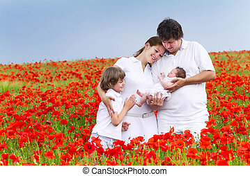 Beautiful young family with two children in a red flower field