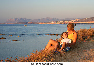 Mother and son relaxing at a beautiful sunset on the beach