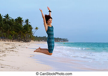 Young beautiful woman jumping on a tropical beach