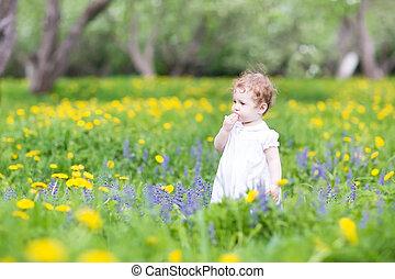 Cute little girl playing in a beautiful garden