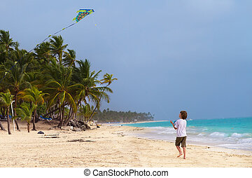 Litte boy playing with a kite on a tropical beach