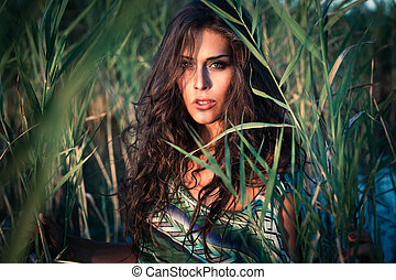 summer fashion - young woman in colorful top stand in river...