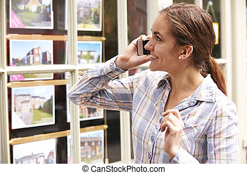 Happy Young Woman On Phone Outside Estate Agents