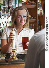 Female Bartender Serving Drink To Male Customer
