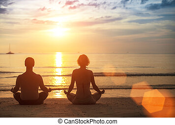 Silhouette of young couple practicing yoga on the sea beach...