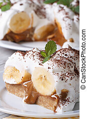 Piece of banana cake with cream close up on the table -...
