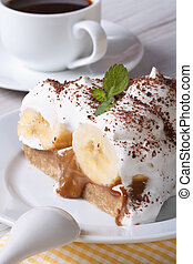 Piece of banana cake with cream and coffee close-up on the...