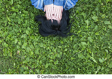 Girl lying on the grass covering eyes with hands, top view.